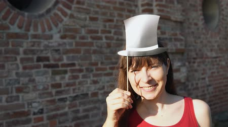 fingir : Young happy woman holds a paper mustache and black retro hat on a stick, dancing next to a brick wall.