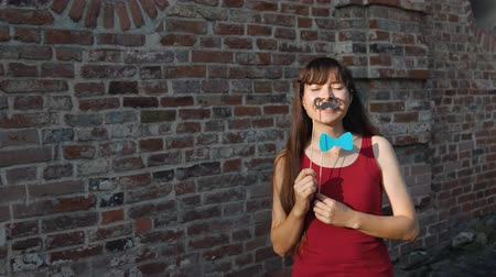ileri : A young happy woman holds a paper black mustache and a a blue bow tie on a stick while standing next to a brick wall.