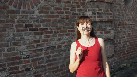 bigode : Young happy woman holds a paper black mustache on a stick, standing next to a brick wall.