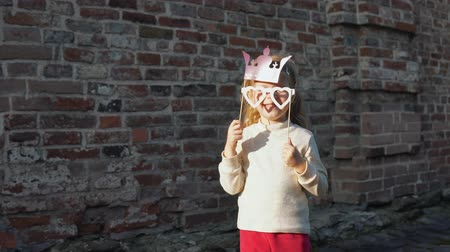 red tie : Little cute girl playing with paper phony glasses and a crown on a stick next to a brick wall.