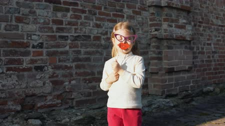 separè : Little cute girl playing paper sham glasses and red lips on a stick next to a brick wall.