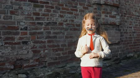 red tie : Little cute girl playing paper mustache and red tie on a stick next to a brick wall. Stock Footage