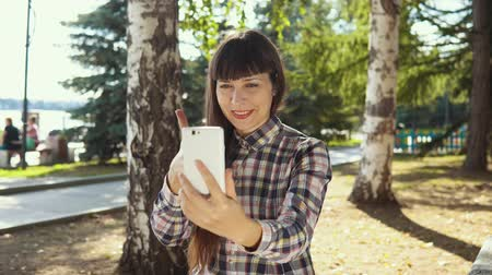 брюнет : Young woman using smartphone in city park, female designer browsing chatting reading news.
