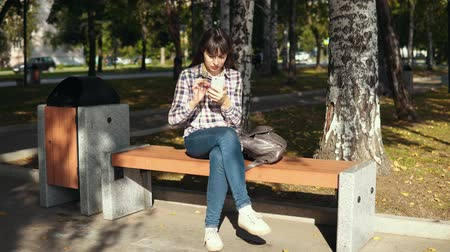 quadriculada : Young woman in checkered shirt using smartphone in city autumn park, female freelancer browsing chatting reading news. Vídeos
