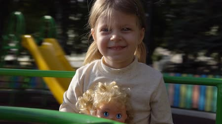 долл : Little cute girl riding a merry-go-round in a city park on a sunny day. Happy child holding a blond doll, slow motion. Стоковые видеозаписи