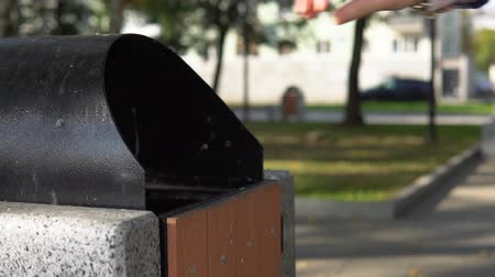 atmak : Someone throws garbage in an urn in a city park, slow motion.