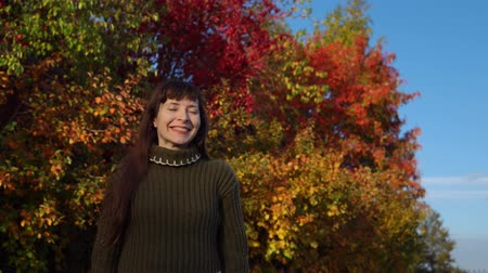wol : A young joyful woman in a green knitted sweater shakes her head against the background of colorful foliage in the city park in the city park in Indian summer.