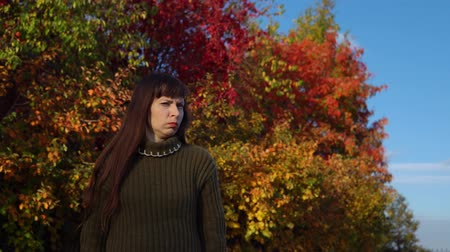 sem camisa : Young displeased woman in a green knitted sweater shakes her head against the background of multicolored foliage in the city park in Indian summer.