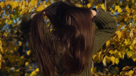 wol : A young woman dressed in a green knitted sweater straightens her long dark hair with her back to the camera on the background of yellow autumn trees. Stockvideo