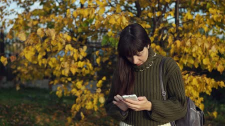 wol : A young woman dressed in a green knitted sweater is viewing messages in the application on a smartphone in the autumn park.