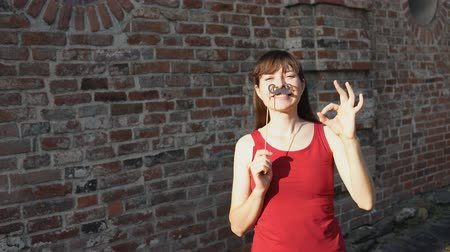 rendes : Young happy woman holds a paper black mustache on a stick and shows gestures of OK, standing next to a brick wall. Stock mozgókép
