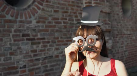 sahte : Young happy woman holds a paper black mustache with retro glasses and dark retro hat on a stick and shows thumb up, standing next to a brick wall.