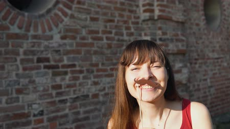 bigode : Young happy woman holds a paper mustache and black retro hat on a stick, dancing next to a brick wall.