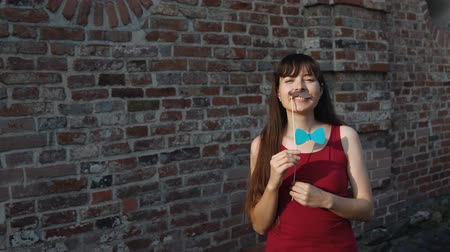 red tie : A young happy woman holds a paper black mustache and a a blue bow tie on a stick while standing next to a brick wall.