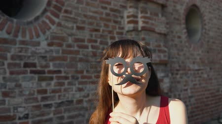 bigode : Young happy woman holds a paper mustache with black retro glasses on a stick, standing next to a brick wall.