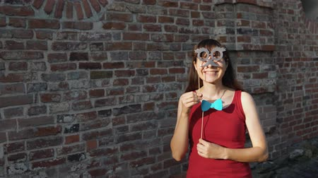 piada : A young happy woman holds a paper black mustache and a a blue bow tie on a stick while dancing next to a brick wall.