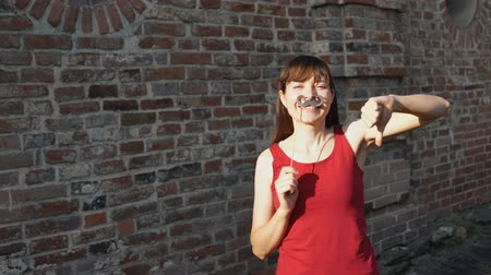 отказ : Young happy woman holds a paper black mustache on a stick and shows thumbs down, standing next to a brick wall. Стоковые видеозаписи