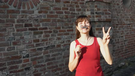 piada : Young happy woman holds a paper black mustache on a stick and shows sign of victory, standing next to a brick wall. Stock Footage