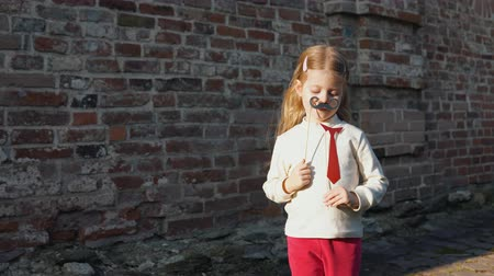 sahte : Little cute girl playing paper mustache and red tie on a stick next to a brick wall. Stok Video