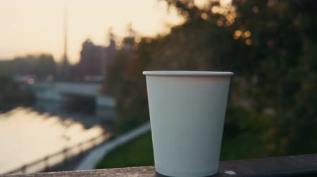 teacup : A white paper cup with coffee or tea stands on the railing against the backdrop of the city park at sunset. A hot drink raises steam. Stock Footage