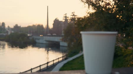 vasárnap : A white paper cup with coffee or tea stands on the railing against the backdrop of the city park at sunset. A hot drink raises steam. Stock mozgókép