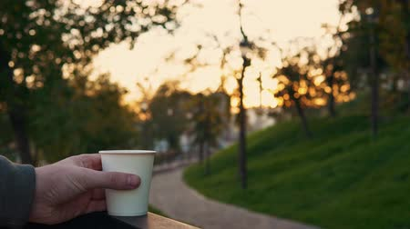 vasárnap : Someone raises a white cup of hot coffee from the railing on the background of the cityscape at sunset Indian summer. Stock mozgókép