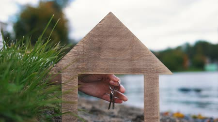 nyaraló : Female hand holds out keys through the window of a wooden model house at the seashore. The concept of suburban life near the water.