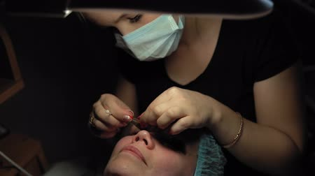 yama işi : Makeup artist doing curling and keratin lash lift for female client, procedure for the care of eyelashes in a beauty salon, dolly shot. Stok Video