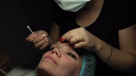 capacidade : Makeup artist doing curling and keratin lash lift for female client, procedure for the care of eyelashes in a beauty salon, dolly shot. Stock Footage