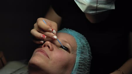 prosedür : Makeup artist doing curling and keratin lash lift for female client, procedure for the care of eyelashes in a beauty salon, dolly shot. Stok Video