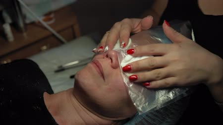 rozšíření : Close up procedure for the care of eyelashes in a beauty salon. Makeup artist doing curling and keratin lash lift for female client, dolly shot.