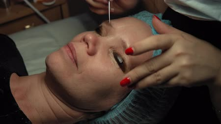 capacidade : Close up procedure for the care of eyelashes in a beauty salon. Makeup artist doing curling and keratin lash lift for female client, dolly shot.