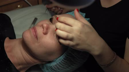 kapasite : Close up procedure for the care of eyelashes in a beauty salon. Makeup artist doing curling and keratin lash lift for female client, dolly shot.