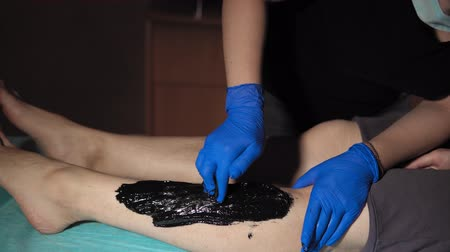 cera : A sugaring is performed using the black paste from the legs of a young woman at a spa. The master molds a ball against the direction of hair growth and pulls the hair in the direction of growth.
