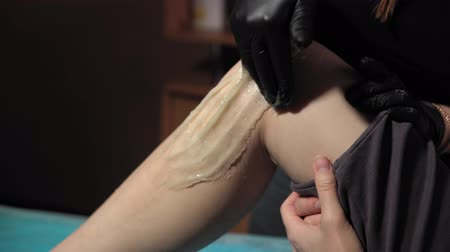 woman waxing : A sugaring is performed using the sugar paste from the legs of a young woman at a spa. The master in black gloves removes the hair in the direction of growth.