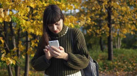 breien : A young woman dressed in a green knitted sweater makes a call using an application on a smartphone in an autumn park.