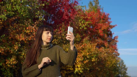 wol : A young woman dressed in a green knitted sweater makes a video call using an application on a smartphone in an autumn park.