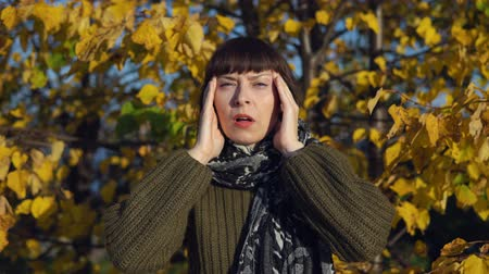 esfregar : A young sick woman in a green knitted sweater strokes her head against the background of yellow foliage in the city park in Indian summer.