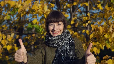 wol : A young woman in a green knitted sweater shows thumbs up against the background of yellow foliage in a city park in Indian summer.