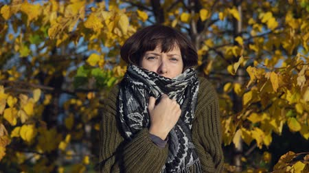 wol : A young woman in a green knitted sweater is wrapped in a warm scarf against the yellow foliage in the city Park in the Indian summer.