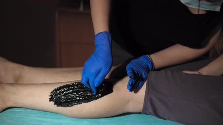 pegar : A sugaring is performed using the black paste from the legs of a young woman at a spa. The master molds a ball against the direction of hair growth and pulls the hair in the direction of growth.