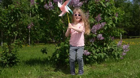 egyetlen virág : A small blonde girl jumps with a colorful pinwheel next to a blooming lilac, slow motion. A serious child is playing with in the green spring garden.