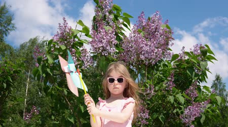 egyetlen virág : A little blonde girl stands with a colorful pinwheel next to a blooming lilac. Smiling child is playing with pleasure in a green spring garden against a blue sky.