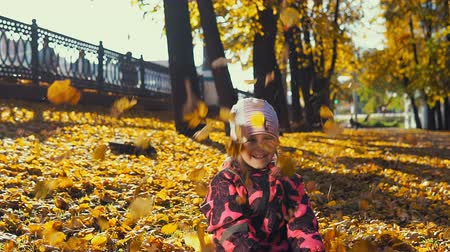 gooien : Little cute girl in pink jumpsuit plays with yellow leaves in the city park in the Indian summer, slow motion.