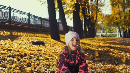 positividade : Little cute girl in pink jumpsuit plays with yellow leaves in the city park in the Indian summer, slow motion.