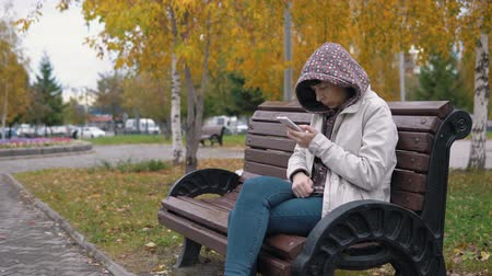 wol : A young woman dressed in a green hoody is viewing messages in the application on a smartphone in the autumn park.