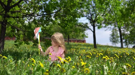 egyetlen virág : Little cute girl playing with a multicolored pinwheel, a happy child is sitting in dandelions on a spring sunny day. Stock mozgókép
