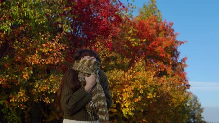 wrzesień : A young woman in a green knitted sweater is wrapped in a warm scarf against the background of colorful foliage in the city park in Indian summer.