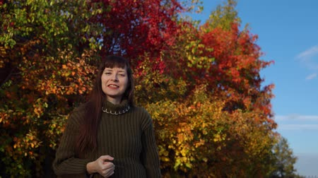 invite : A young joyful woman in a green knitted sweater beckons someone, shows a hand gesture against the background of colorful foliage in the city park in Indian summer. Stock Footage