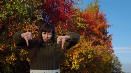 wol : A young woman in a green knitted sweater shows thumbs down against the background of multicolored foliage in a city park in Indian summer. Stockvideo